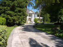 White mansion in park like setting. Older mansion set in a park like front yard. Paved road leads to the entrance, lush vegetation, palm trees and blue Royalty Free Stock Photography