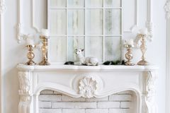 White mantelpiece with candles and christmas decorations. Classic interior. White mantelpiece with candles and christmas decorations. Classic interior Royalty Free Stock Photos