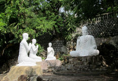 White marble Buddha statue sitting. Big white marble Buddha statue sitting and monks praying. Buddha statue in a Buddhist temple, standing outside. Sacred relic Stock Photo