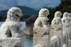 White Marble Carved Lions. In the Summer Palace, these 544 carved white marble lions, in distinctive postures, sit at the column of the parapets on the 17-arch stock images