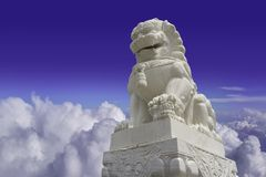 White marble Chinese guardian lion sculpture on blue and cloudy sky background with clipping path.  stock images