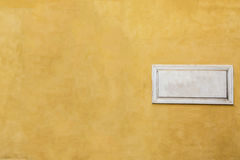 White marble classic blank nameplate with empty space for text. And numbers on yellow painted wall of old Italian house in Rome. Vintage background with Stock Images