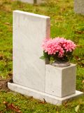 White marble gravestone from behind with pink flowers cemetery Stock Photo