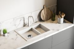 White marble kitchen sink, top view. Top view of white marble kitchen sink standing on gray countertop in room with white walls. Wooden round cutting board and royalty free illustration