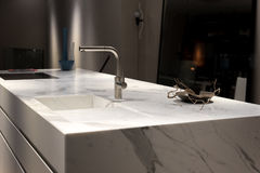 White Marble Kitchen. Stylish Solid White Marble Kitchen Counter With Dark Cupboards Stock Photos