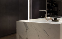 White Marble Kitchen. Stylish Solid White Marble Kitchen Counter With Dark Cupboards Stock Image