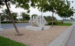 White Marble Layered Squares. White Marble Layered Square sculpture, along road side with green carpet grass garden and brown rock gravel Stock Images