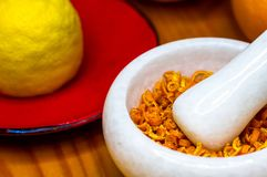 White marble mortar with the orange zest. White marble mortar and pestle with the dried orange zest Stock Photography