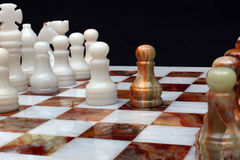 White marble and onyx stone chessboard with pieces on black back Royalty Free Stock Photography