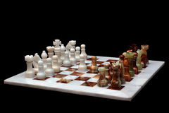 White marble and onyx stone chessboard with pieces, isolated on black background Royalty Free Stock Images