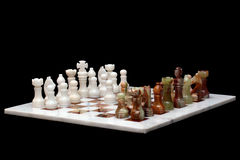 White marble and onyx stone chessboard with pieces, isolated on black background Stock Images