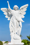 White marble statue of a young female angel. Beautiful white marble statue of a young female angel on a clear sunny day with a blue sky background Royalty Free Stock Photos