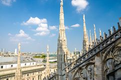 White marble statues on roof of Duomo di Milano Cathedral, Italy. White marble statues on roof of famous Duomo di Milano Cathedral and top aerial view of Milan stock image