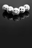 White marbles with faces. On a black stone with reflections. concept teamwork and success Stock Photo
