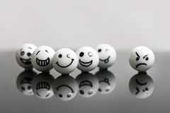 White marbles with faces. On a black stone with reflections. concept teamwork and success with one misfit Stock Photo