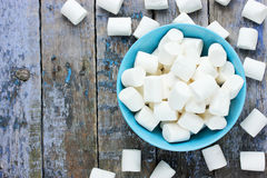 White marshmallow in blue bowl on old wooden table Royalty Free Stock Photos