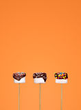 White marshmallow dipped in chocolate. White marshmallow in chocolate on orange background Royalty Free Stock Photos