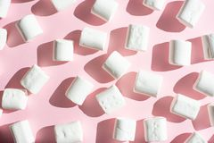White marshmallow on a pink background, with hard shadows. Possibility to use as a background,Winter food background concept.Flat. Lay or top view colors eat royalty free stock photos