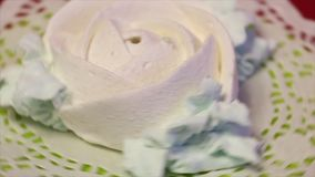 White marshmallows in the shape of a rose. With petals. Lies on a lacy napkin. Rotates around a vertical axis stock footage