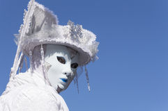 White mask at carnival in Venice. A white woman with a mask representing the winter, under a blue sky in Venice, Italy Royalty Free Stock Photo