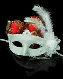 White mask and Christmas red balls on a black background Stock Photos