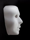 White mask emerging from black background Stock Image