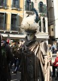 A white mask with golden details next to the eyes Venice Carnival 2019. Venice Carnival 2019. A white mask with golden details next to the eyes. A man in a suit stock images