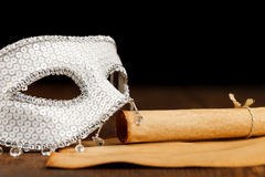 White mask with old paper scroll. White glittering mask with old paper scroll and paper on wooden table Royalty Free Stock Photos