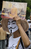White Mask with photo of King. BANGKOK, July 14: White-Mask protestor shows a photo of ther King as a monk when anti-government protestors supporting the white Stock Image