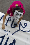 White Mask protestor paints on banner Royalty Free Stock Photo