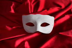 White mask on red background. White mask lying on red satin royalty free stock photography