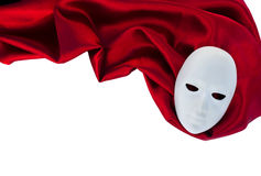 White mask on red silk fabric. Theatre concept Royalty Free Stock Photo