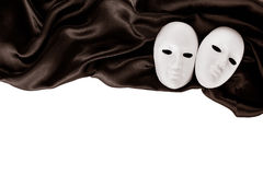 White masks and black silk fabric Stock Photo