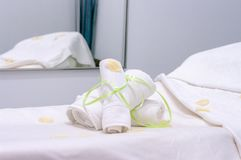 Two white towels rolled and fastened with green tape on massage table and mirror on the wall. White massage cabin with massage table and two white rolled towels stock photo