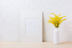 White mat frame mockup with ornamental yellow flowering grass in Stock Photos