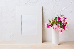 White mat frame mockup with pink and purple flower bouquet stock image