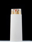White matches in box with one red head on black Royalty Free Stock Image