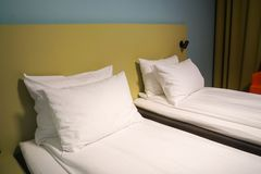 White mattress and comfortable pillows in hotel twin bedroom stock photo