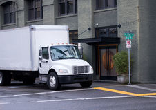 White mddle size delivery semi truck with box trailer on city st. Modern white semi truck of middle duty and size with day cab and box trailer for local Royalty Free Stock Photos