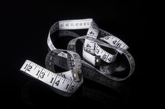 White measuring tape on black with reflection Royalty Free Stock Photo
