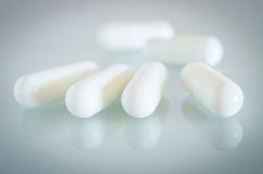 White medical capsules lie on the mirror surface Royalty Free Stock Image
