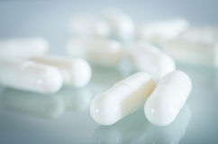 White medical capsules lie on the mirror surface Stock Photo