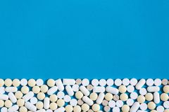 White Medical Pills On Blue Background With Copy-Space. Top view. Creativity Concept. White Medical Pills On Blue Background With Copy-Space. Top view royalty free stock photos