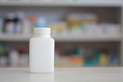 White medicine bottle with blur shelves of drug in the pha Royalty Free Stock Photo