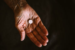 Medicine pill or tablet in hand of old woman Royalty Free Stock Photos
