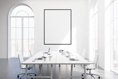 White meeting room interior, poster. Loft meeting room interior with white walls, a concrete floor, two long white tables with laptops on them and a vertical Royalty Free Stock Photos