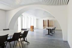 White meeting room. Nobody inside. Large white meeting room with desk and black chairs. Nobody inside royalty free stock photo
