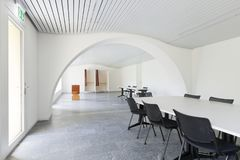 White meeting room. Nobody inside. Large white meeting room with desk and black chairs. Nobody inside stock photography