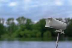 White megaphone on a mast against nature scene. With a lake water, forest and blue sky stock photos