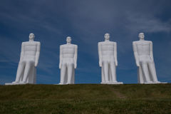 White Men, Esbjerg, Denmark. Four white men sitting looking at the sea near Esbjerg, Denmark. They are each 9 meters tall and made of white concrete Stock Image
